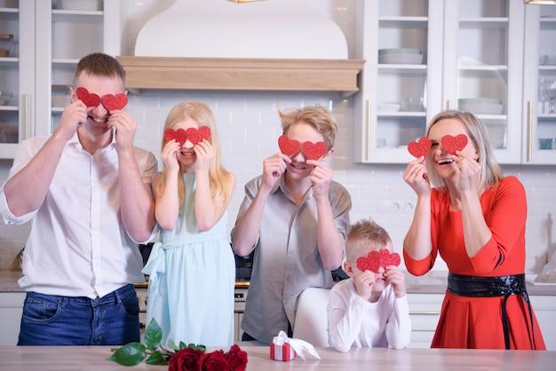 Felice famiglia completa di papà mamma e tre bambini due ragazzi e ragazze è in possesso di cuori di carta rossa e sorridente, la famiglia è in piedi in cucina a casa, gente caucasica bionda. san valentino e amore.