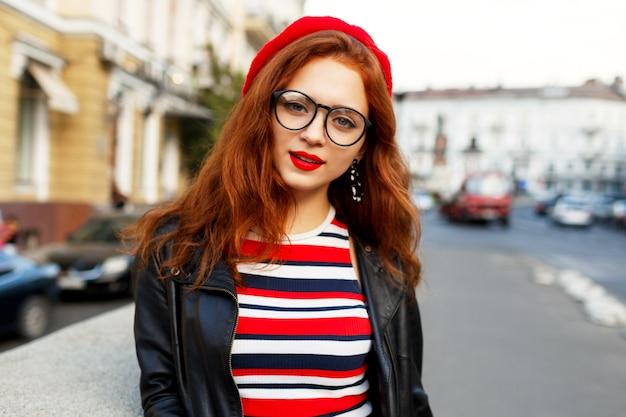 Felice favolosa donna allo zenzero in elegante berretto rosso in strada