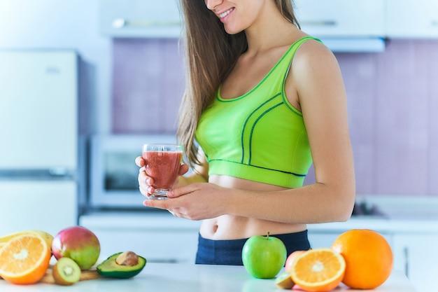 Felice femmina dieta fitness in abiti sportivi beve un frullato di frutta fresca per perdere peso. bevande vitaminiche per un'alimentazione sana