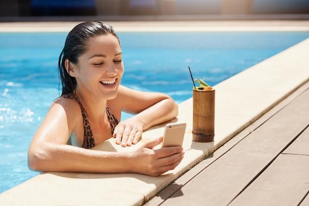 Felice femmina sorridente con i capelli bagnati, tenendo in mano il moderno smart phone, rilassarsi a bordo piscina e bere cocktail analcolico