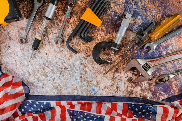 Felice festa del lavoro con bandiera americana e strumenti di costruzione