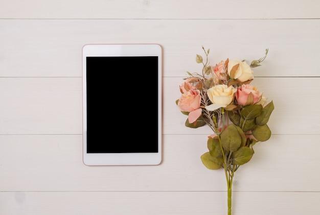 Felice festa della mamma o san valentino con display in bianco tablet e fiori sul tono pastello tavolo in legno, sentirsi romantico con la decorazione