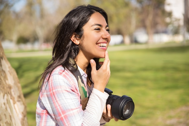 Felice fotografo femminile allegro divertendosi