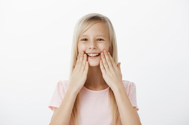 Felice ghignante adorabile bambino con i capelli biondi, sorridente ampiamente e tenendo i palmi vicino alle labbra, stupito e soddisfatto di denti sani, frequentando il dentista e sentendosi felice