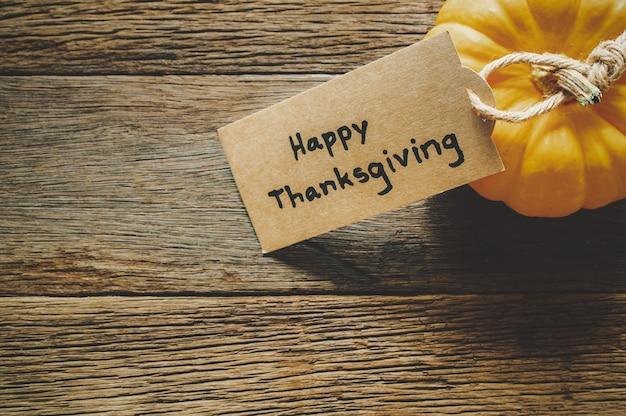 Felice giorno del ringraziamento sfondo con zucca e saluto tag sul tavolo di legno