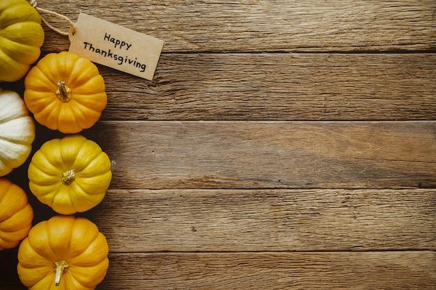 Felice giorno del ringraziamento sfondo con zucche e saluto tag sul tavolo di legno