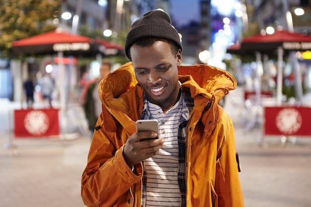 Felice giovane afro-americano vestito elegantemente in cappotto invernale e cappello avendo sera a piedi da solo per le strade della città straniera, gli amici di messaggistica sul gadget elettronico. persone e tecnologia moderna