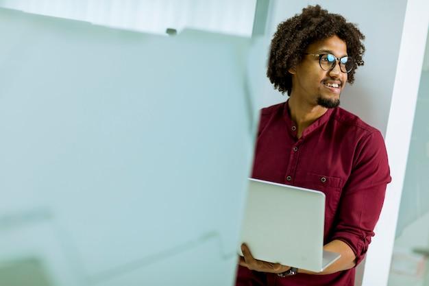 Felice giovane afroamericano it specialista con gli occhiali che lavorano sul suo computer portatile in ufficio