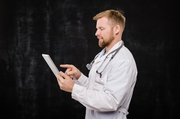 Felice giovane barbuto medico in mantello bianco che scorre nel touchpad o che indica lo schermo mentre si lavora in isolamento