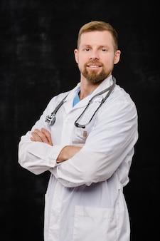 Felice giovane barbuto medico in whitecoat incrocio le braccia sul petto mentre ti guarda su sfondo nero