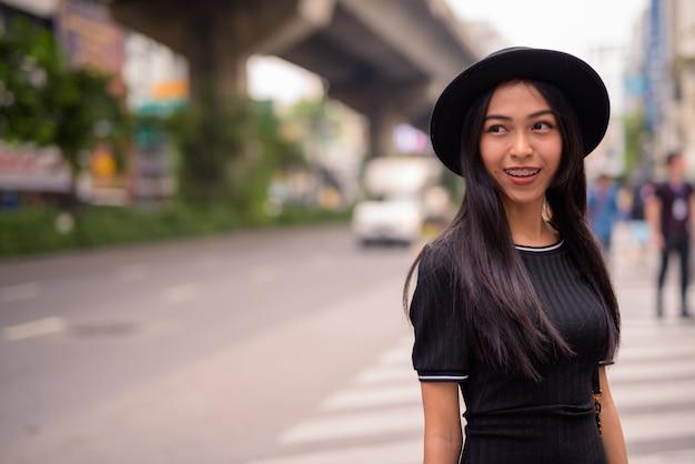 Felice giovane bella donna turistica asiatica nelle strade della città