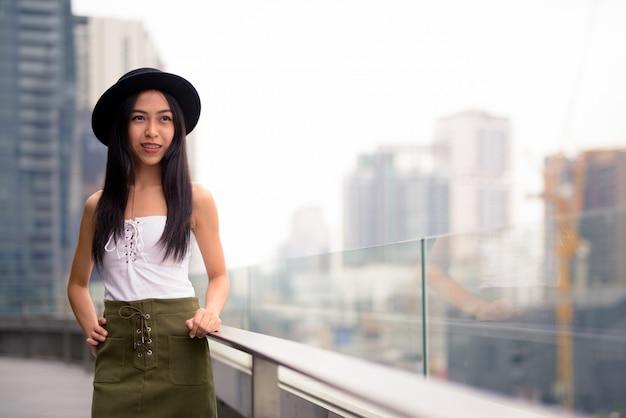 Felice giovane bella donna turistica asiatica pensando contro la vista della città