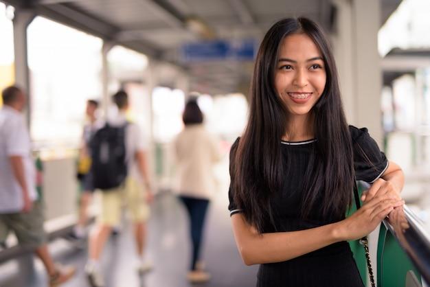 Felice giovane bella donna turistica asiatica pensando sulla passerella