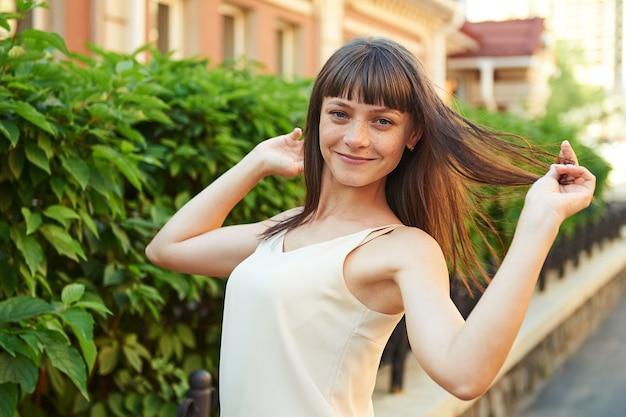 Felice giovane bruna con le lentiggini sul viso in una giornata di sole