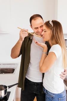 Felice giovane che lascia sua moglie assaggiare una zuppa con un cucchiaio di legno in cucina