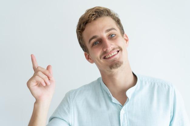 Felice giovane che punta il dito verso l'alto. bel ragazzo che consiglia qualcosa.