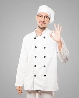 Felice giovane chef facendo un gesto va bene