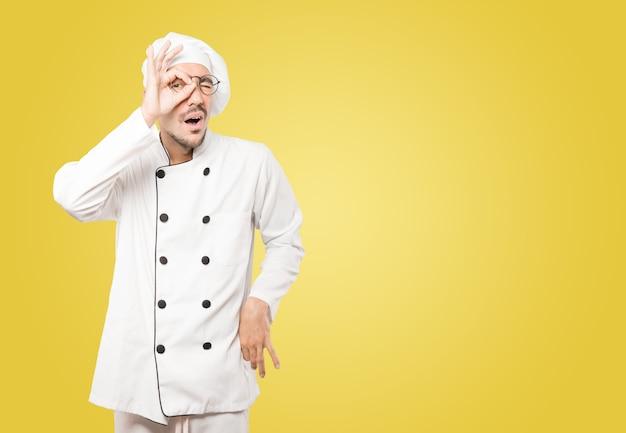 Felice giovane chef usando le mani come un binocolo