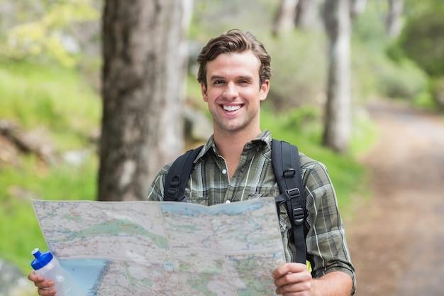 Felice giovane con mappa sul sentiero