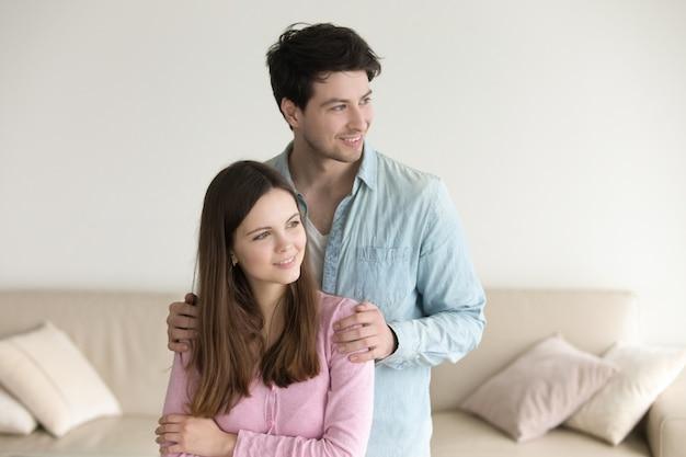 Felice giovane coppia a casa, in piedi insieme, sorridendo, guardando