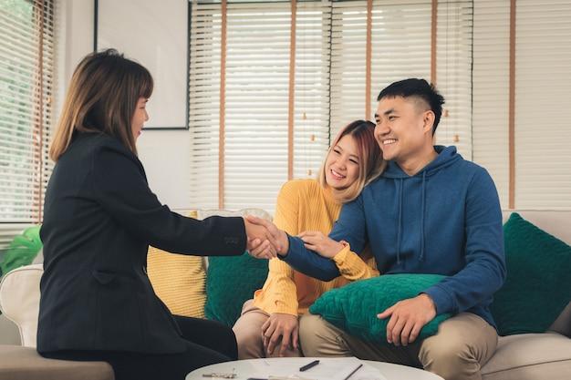 Felice giovane coppia asiatica e agente immobiliare