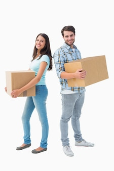 Felice giovane coppia con scatole in movimento