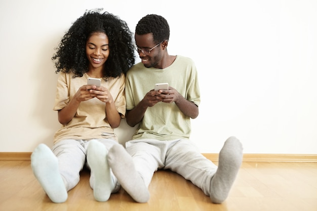 Felice giovane coppia di sposi africani divertendosi insieme a casa, godendo della connessione wireless gratuita, utilizzando i telefoni cellulari. uomo con gli occhiali sorridente