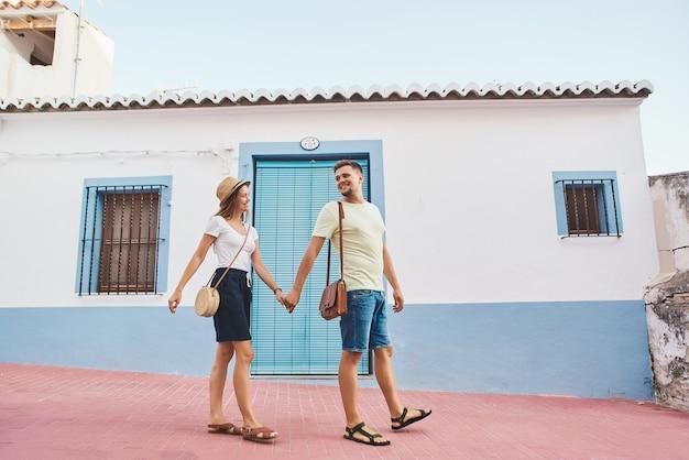 Felice giovane coppia di viaggiatori a piedi