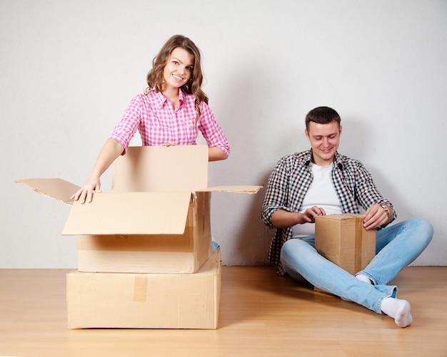 Felice giovane coppia disimballaggio o imballaggio scatole e trasferirsi in una nuova casa.