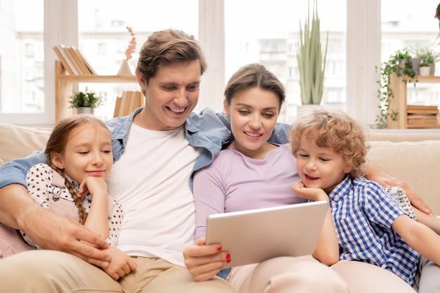 Felice giovane coppia e i loro due bambini in abbigliamento casual rilassante insieme sul divano