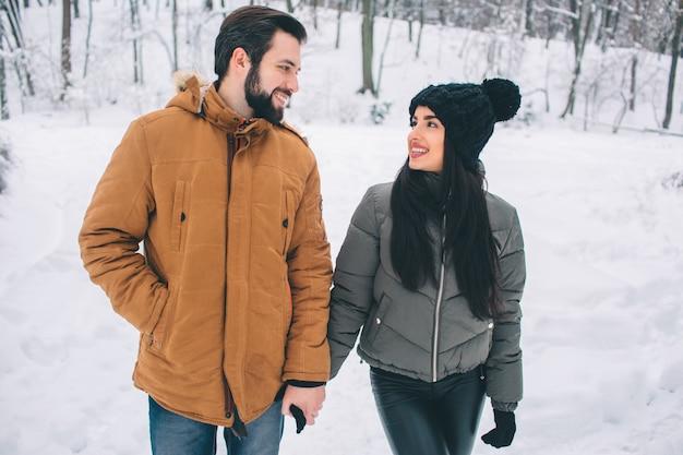 Felice giovane coppia in inverno. famiglia all'aperto. uomo e donna guardando verso l'alto e ridendo. amore, divertimento, stagione e persone - passeggiate nel parco invernale. alzati e tieniti per mano