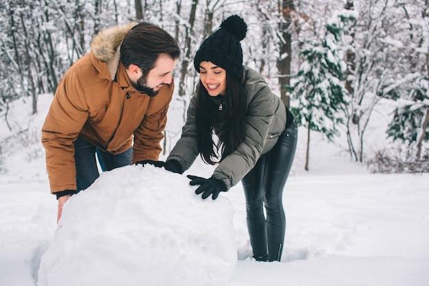 Felice giovane coppia in inverno. famiglia all'aperto. uomo e donna guardando verso l'alto e ridendo. amore, divertimento, stagione e persone - passeggiate nel parco invernale. fare un pupazzo di neve.