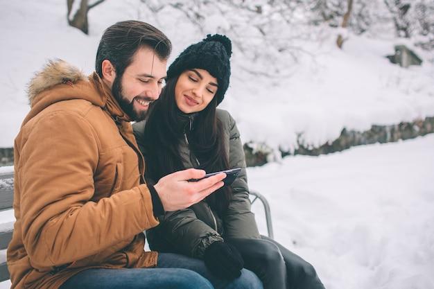 Felice giovane coppia in inverno. famiglia all'aperto. uomo e donna guardando verso l'alto e ridendo. amore, divertimento, stagione e persone - passeggiate nel parco invernale. siediti sulla panchina. contiene uno smartphone.
