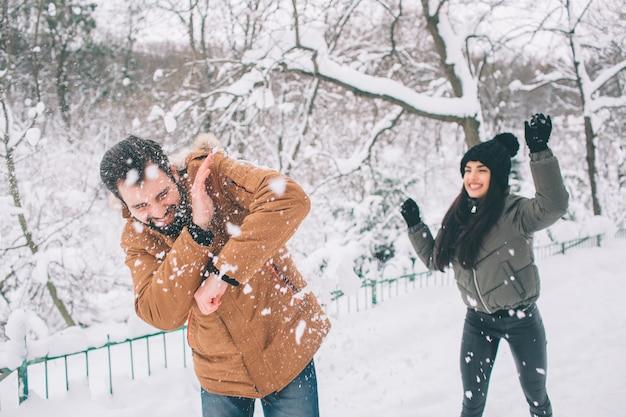 Felice giovane coppia in inverno. famiglia all'aperto. uomo e donna guardando verso l'alto e ridendo. amore, divertimento, stagione e persone - passeggiate nel parco invernale. sta nevicando