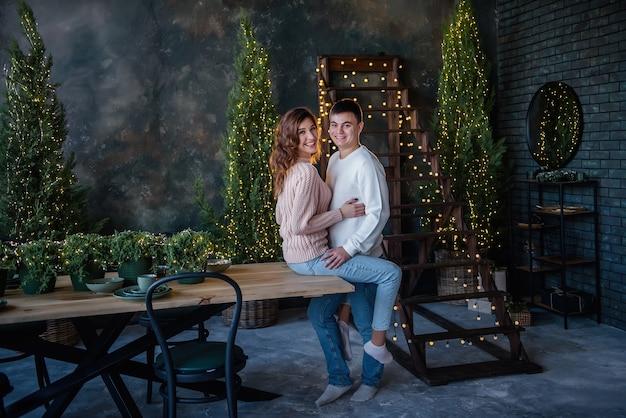 Felice giovane coppia indossando abiti invernali in camera decorata con luci di natale