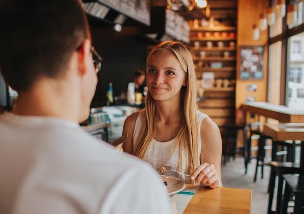 Felice giovane coppia innamorata che ha un appuntamento piacevole in un bar o in un ristorante. raccontano storie su se stessi, bevono tè o caffè e mangiano insalata e zuppa.