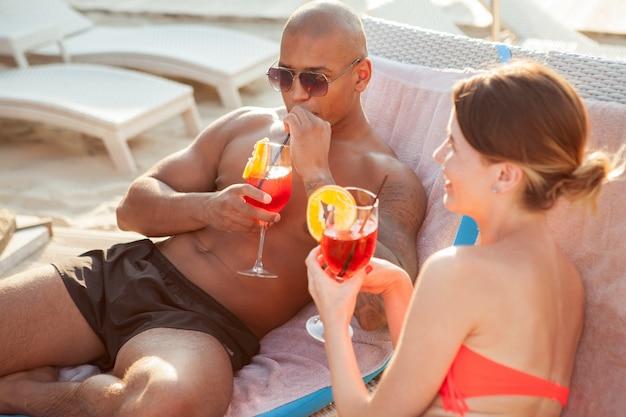 Felice giovane coppia multietnica di relax in spiaggia insieme, con cocktail. uomo africano atletico sorseggiando il suo drink, godendo le vacanze estive al mare con la fidanzata