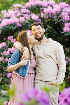 Felice giovane coppia sorridente. si abbracciano e riposano in primavera in un giardino fiorito di rododendri