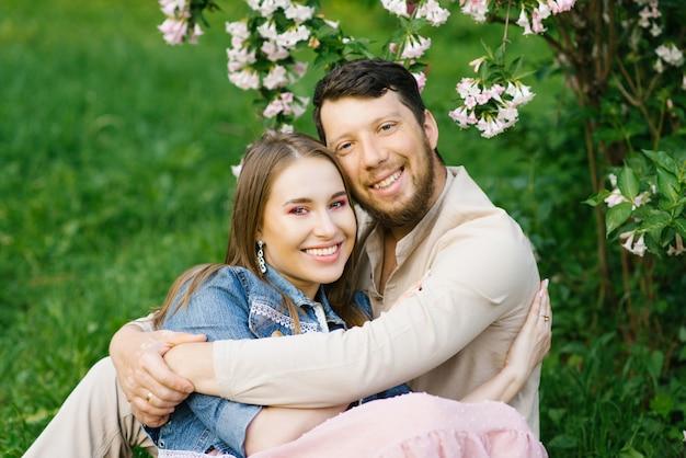 Felice giovane coppia sorridente. si abbracciano e si rilassano in primavera nel parco