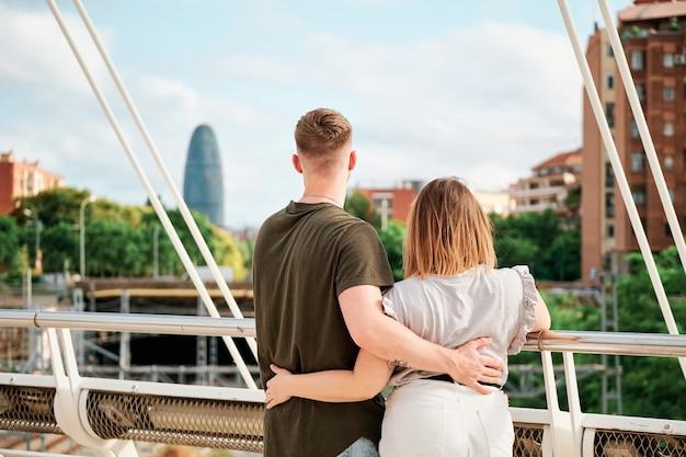 Felice giovane coppia, un bell'uomo e un modello sinuoso, in un ponte guardando lo skyline di barcellona