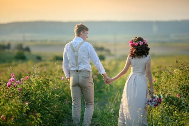 Felice giovane coppia uomo e donna, famiglia romantica adulta. incontra il tramonto in un campo di grano. sorridendo felice. la ragazza tra le mani tiene un regalo, un mazzo di fiori, di rose.