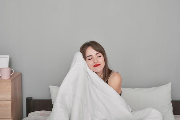 Felice giovane donna a letto a casa camera da letto sotto la coperta.