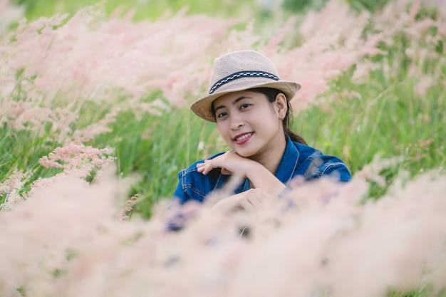 Felice giovane donna asiatica seduta sul campo in erba
