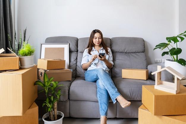 Felice giovane donna asiatica utilizza lo smartphone con la pila di scatole di cartone