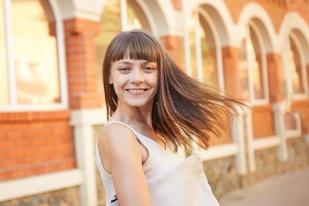 Felice giovane donna bruna con le lentiggini sul viso in una giornata di sole