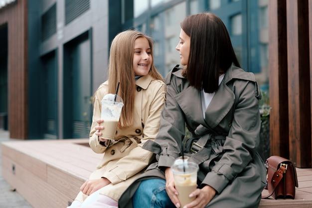 Felice giovane donna casual e sua figlia con bevande guardando a vicenda durante la chat