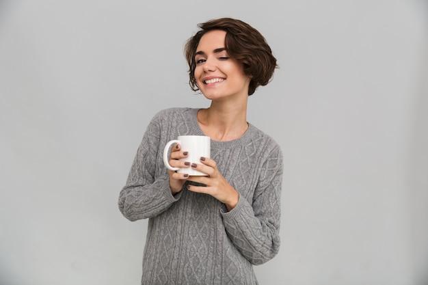Felice giovane donna che beve il tè.