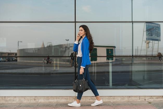 Felice giovane donna che parla al telefono e camminare