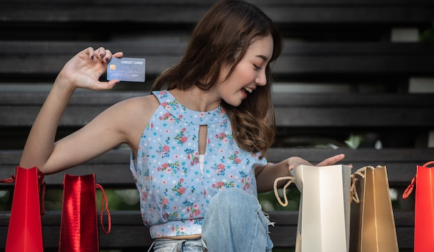 Felice giovane donna con carta di credito con borse della spesa, spendere soldi con godendo per lo shopping.