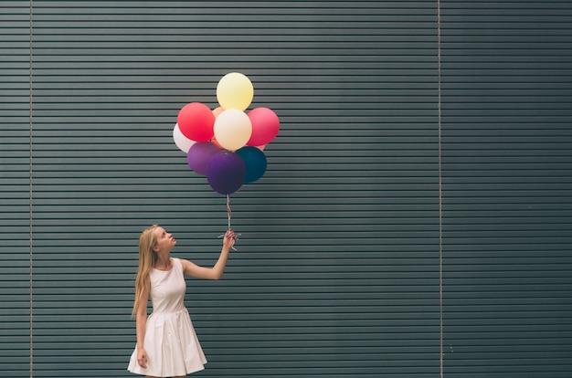 Felice giovane donna con palloncini colorati su una strada vicino al muro grigio